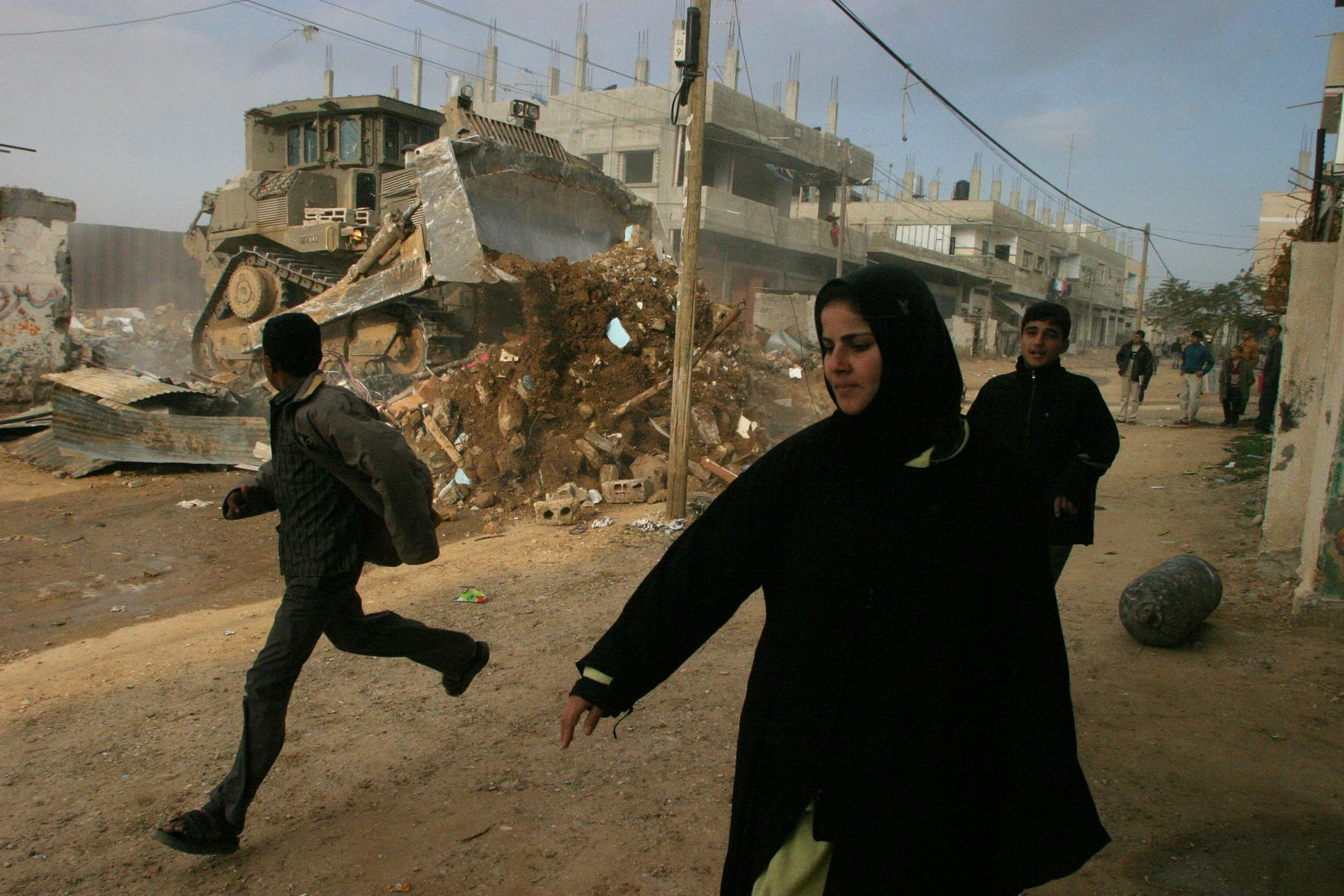 Palestinians run infront an israeli bulldozer as it destroy houses next to the border of Egypt at the Rafah refugee camp in the southern of Gaza Strip . Tusday Jan. 20.2004. (AP Photo/Khalil Hamra).